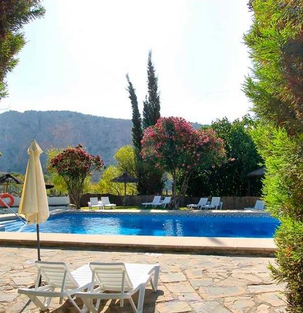 Piscina y sol con vistas a montañas andaluzas